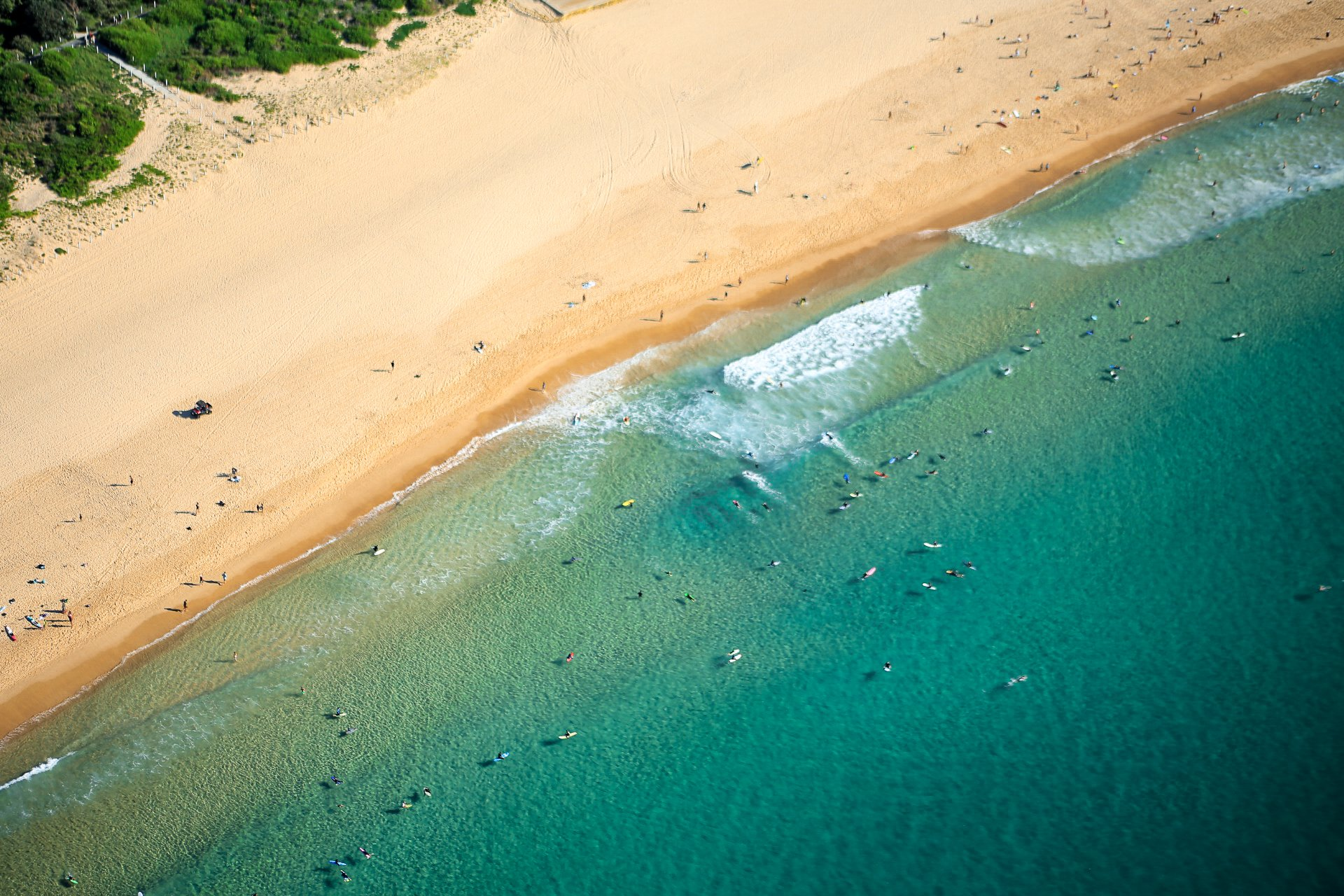 Beach from above with surfers and swimmers